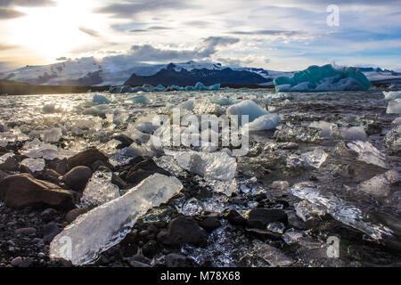 Icebergs on the glacial lake at sunset on Jökulsárlón glacial lagoon, Vatnajokull National Park, Iceland - Stock Photo