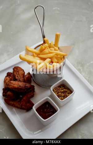 Chicken wings with sauce ketchup and fries in a metal stand on parchment paper - Stock Photo