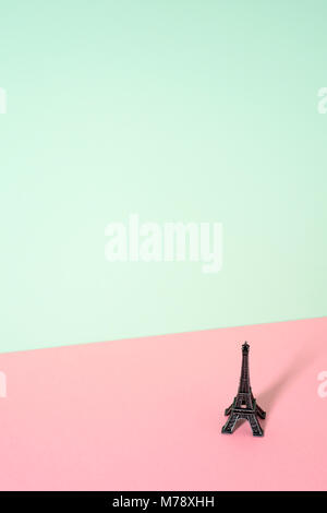 a miniature of the miniature of Eiffel Tower in a colorful pink and green background, with a large blank space on - Stock Photo