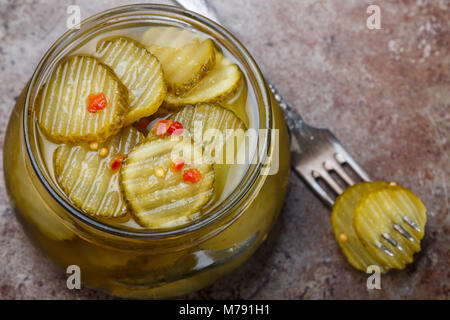 Slices of pickled cucumbers with pepper and mustard in a jar. Snack for gourmets. Selective focus - Stock Photo