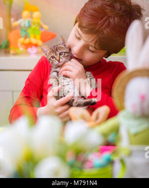 Portrait of a cute boy with his nice little pet friend having fun at home, adorable child playing with small cat, - Stock Photo