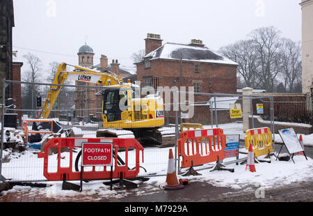 Footpath closed sign barriers road works at junction of The Close and Beacon Street on snowy day in Lichfield  Yellow - Stock Photo