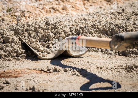 Cement and water being mixed on ground with shovel to get wet cement on construction site, to use to hold blocks - Stock Photo
