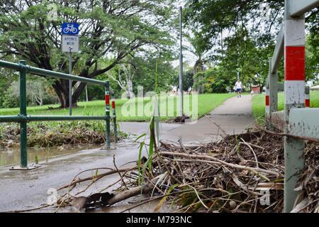 Debris lies over a pedestrian path after storms and heavy rainfall and flooding, near Aplins weir, Townsville, Queensland, - Stock Photo