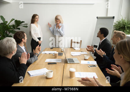 Senior woman boss introducing new worker, team welcoming at meet - Stock Photo