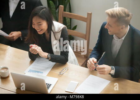 Attractive asian businesswoman and caucasian businessman laughin - Stock Photo