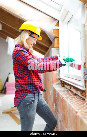 beautiful woman with yellow helmet is working in her loft - Stock Photo
