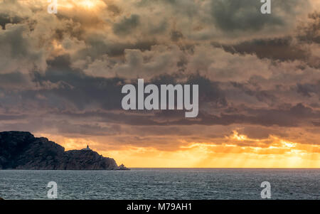 Evening sun rays bursting through dark stormy clouds onto the Mediterranean sea behind the Revellata lighthouse - Stock Photo
