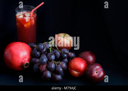 Dark Food - Chiaroscuro pomegranite, grapes, apple and plums with fruit punch on dark backround with copy space - Stock Photo