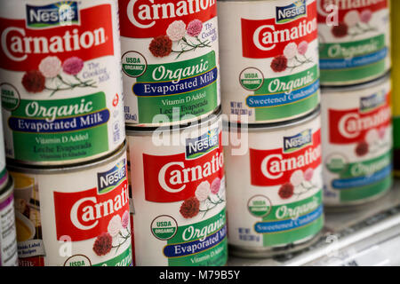 Cans of Nestle Foods products, Carnation Evaporated Milk and Carnation Sweetened Condensed Milk, both organic, are - Stock Photo