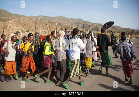 Oromo men and boys with sticks, Canes and weapons dancing and celebrating happily a wedding, Oromo region, Sambate, - Stock Photo