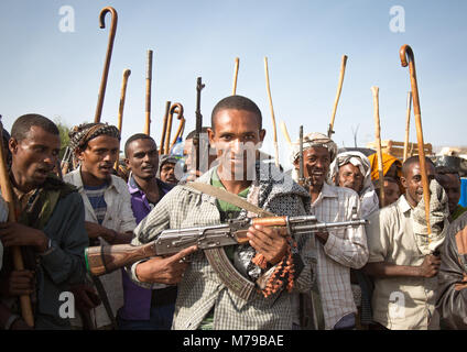 Oromo man proudly displaying his kalachnikov during a wedding here all men and boys are holding sticks, Canes and - Stock Photo