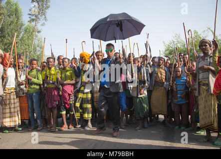 An oromo groom wearing sunglasses and an umbrella, Dancing and celebrating happily his wedding with his relatives - Stock Photo