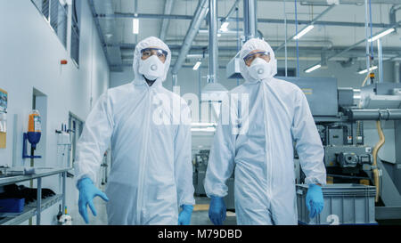 Two Engineers/ Scientists in Hazmat Sterile Suits Walking Through Technologically Advanced Factory/ Laboratory. - Stock Photo