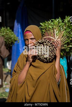 Woman purchasing khat in awaday khat market near harar, The khat capital of the world, Harari region, Awaday, Ethiopia - Stock Photo