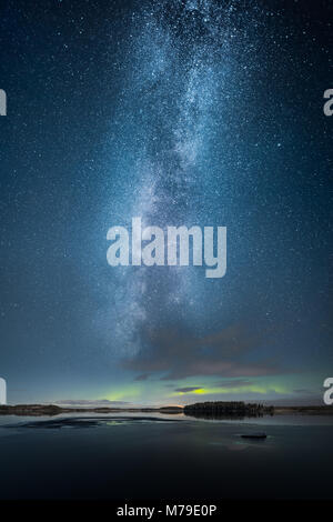 Aurora Borealis aka Northern Light above partly iced lake - Stock Photo