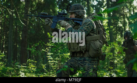 Squad of Fully Equipped Soldiers in Camouflage on a Reconnaissance Military Mission, Aiming Rifles. They're Moving - Stock Photo