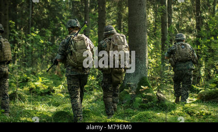 Squad of Five Fully Equipped Soldiers in Camouflage on a Reconnaissance Military Mission, Rifles in Firing Position. - Stock Photo