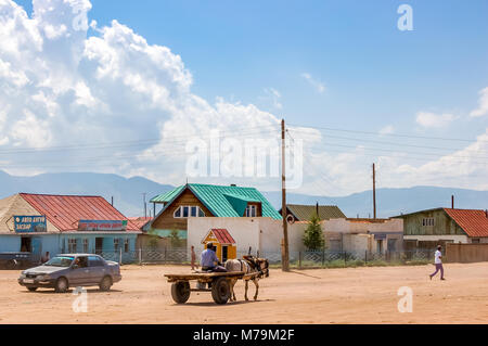 Shine-Ider District, Mongolia -  July 22, 2010: Local man drives horse & cart in tiny, remote community on steppe - Stock Photo
