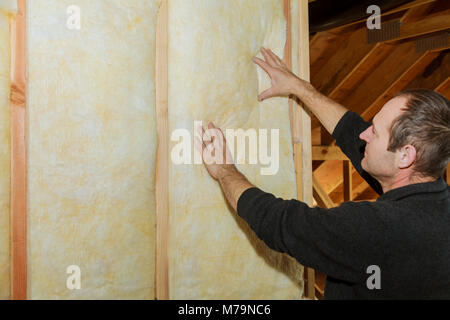 Installation of thermal and hidro insulation Inside wall insulation in wooden house, building under construction - Stock Photo