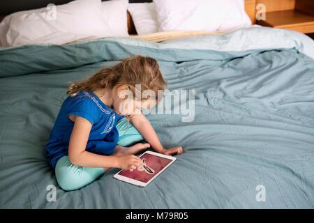 A girl using an ipad mini to learn how to write. - Stock Photo