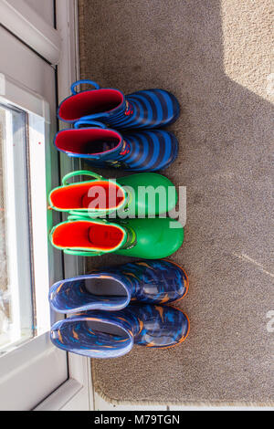 Young childrens colorful wellies sat on a mat by the back door - Stock Photo