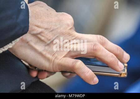 human hand touching a mobile phone - Stock Photo