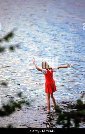 A young girl in a red dress at summer camp dips her toes into the cold water of a lake near her campground. - Stock Photo