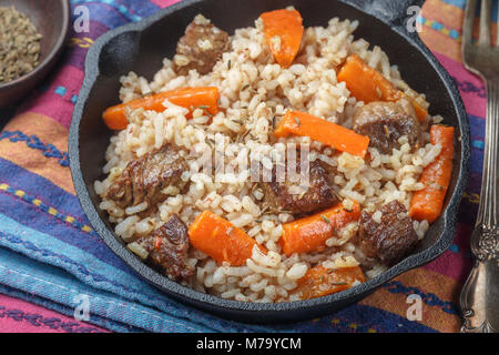 Devzira pilaf with lamb, onions, carrots and spices (cumin, coriander, pepper). Traditional dishes of Uzbek cuisine. - Stock Photo