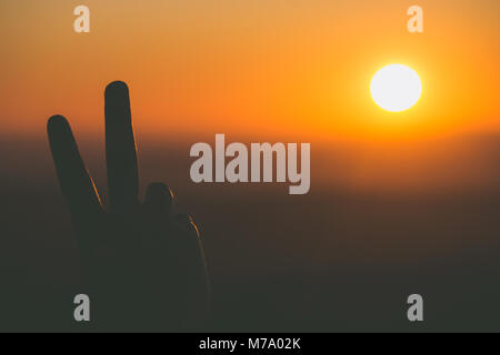 A peace sign hand gesture is silhouetted by the setting sun in Dartmoor, UK - Stock Photo