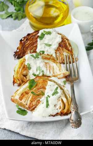 Baked pieces of cabbage with spices and yoghurt sauce, mustard and herbs. Selective focus - Stock Photo