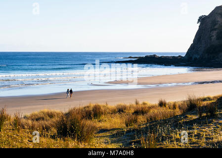 Couple walking on beach at Tapotupotu Bay, near Cape Reinga, North Island, New Zealand - Stock Photo