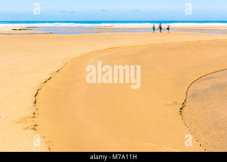 Walkers on Ninety Mile Beach, North Island, New Zealand - Stock Photo