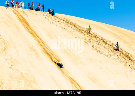 Sand-boarding on giant dunes by the Te Paki Stream, close to Ninety Mile Beach, North Island, New Zealand - Stock Photo