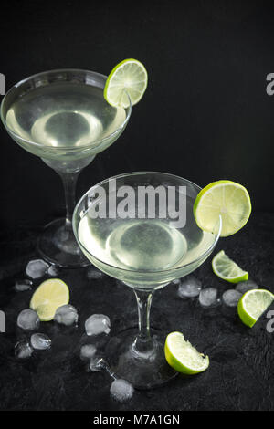 Margarita Сocktail with lime and ice on black stone table, copy space. Classic Margarita Cocktail. - Stock Photo