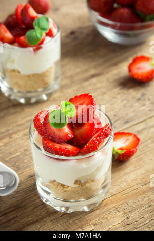 Strawberry cheesecake in glasses with fresh strawberries and cream cheese  on wooden background. Healthy homemade - Stock Photo