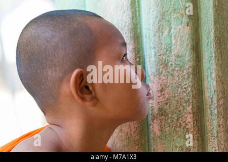 young novice monk face watching television at Aung Myae Oo Monastic Free Education School, Sagaing, Mandalay, Myanmar - Stock Photo