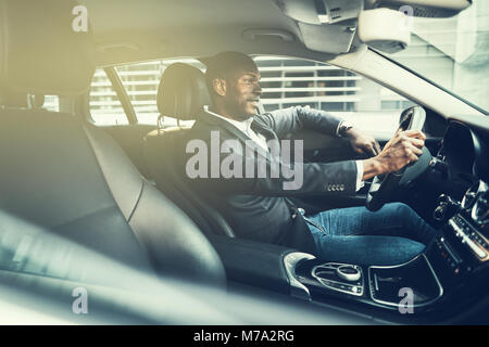 Smiling African businessman wearing a blazer driving his car during his morning commute to work through the city - Stock Photo