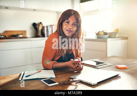 Young African female entrepreneur smiling confidently while working at a table in her kitchen at home - Stock Photo