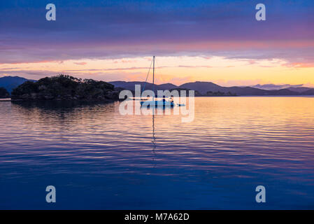 Sunset with anchored yacht off Urupukapuka Island in the Bay of Islands, North Island, New Zealand - Stock Photo
