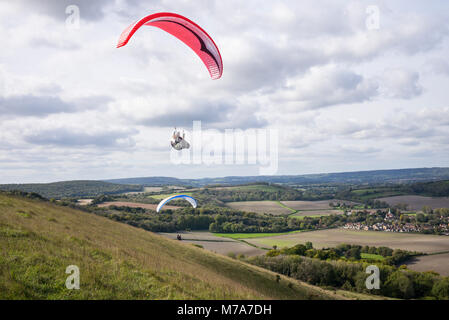 Paraglider flying above the north facing escarpment slope on Harting Down, West Sussex, UK. South Downs National - Stock Photo