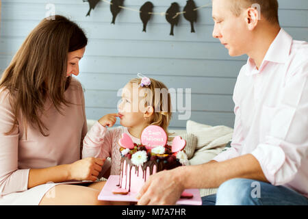 Parents with a little cute daughter. Girl is trying the cake with her finger - Stock Photo