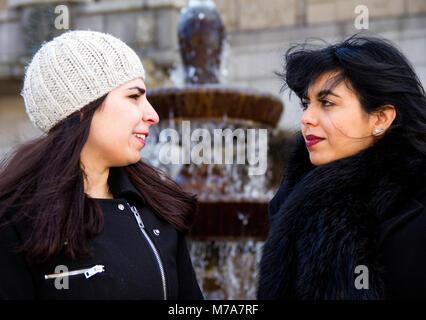Two female students, Parisian-Algerian Faiza Faa (right) with her Iraqi friend Samar Munaf (left) sitting together - Stock Photo