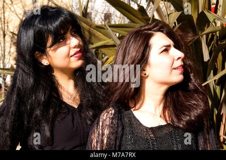 Two female students, Parisian-Algerian Faiza Faa (left) with her friend Samar Munaf from Iraq (right) looking up - Stock Photo