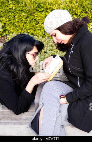 Two female students, Parisian-Algerian Faiza Faa (left) reading a book while relaxing with her Iraqi friend Samar - Stock Photo