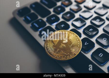 Bitcoin gold coin on computer keyboard backlit - Stock Photo