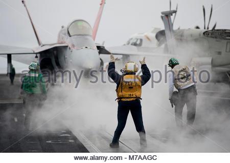 McDonnell Douglas FA-18C Hornet. U.S. Navy Aviation Boatswain's Mate 2nd Class Tamara Sewell, center, directs an - Stock Photo