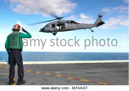 Sikorsky MH-60S Seahawk. U.S. Navy Aviation Electrician's Mate 3rd Class Jeovanny Laureano salutes a  Sikorsky MH - Stock Photo