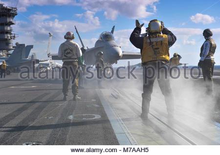 McDonnell Douglas FA-18C Hornet. U.S. Navy Aviation Boatswain's Mate (Handling) 2nd Class Tamara Sewell, foreground, - Stock Photo