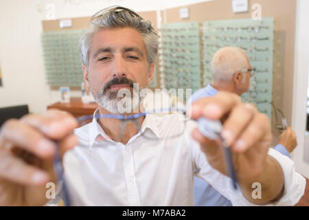handsome ophthalmologist handing over pair of eye glasses to patient - Stock Photo